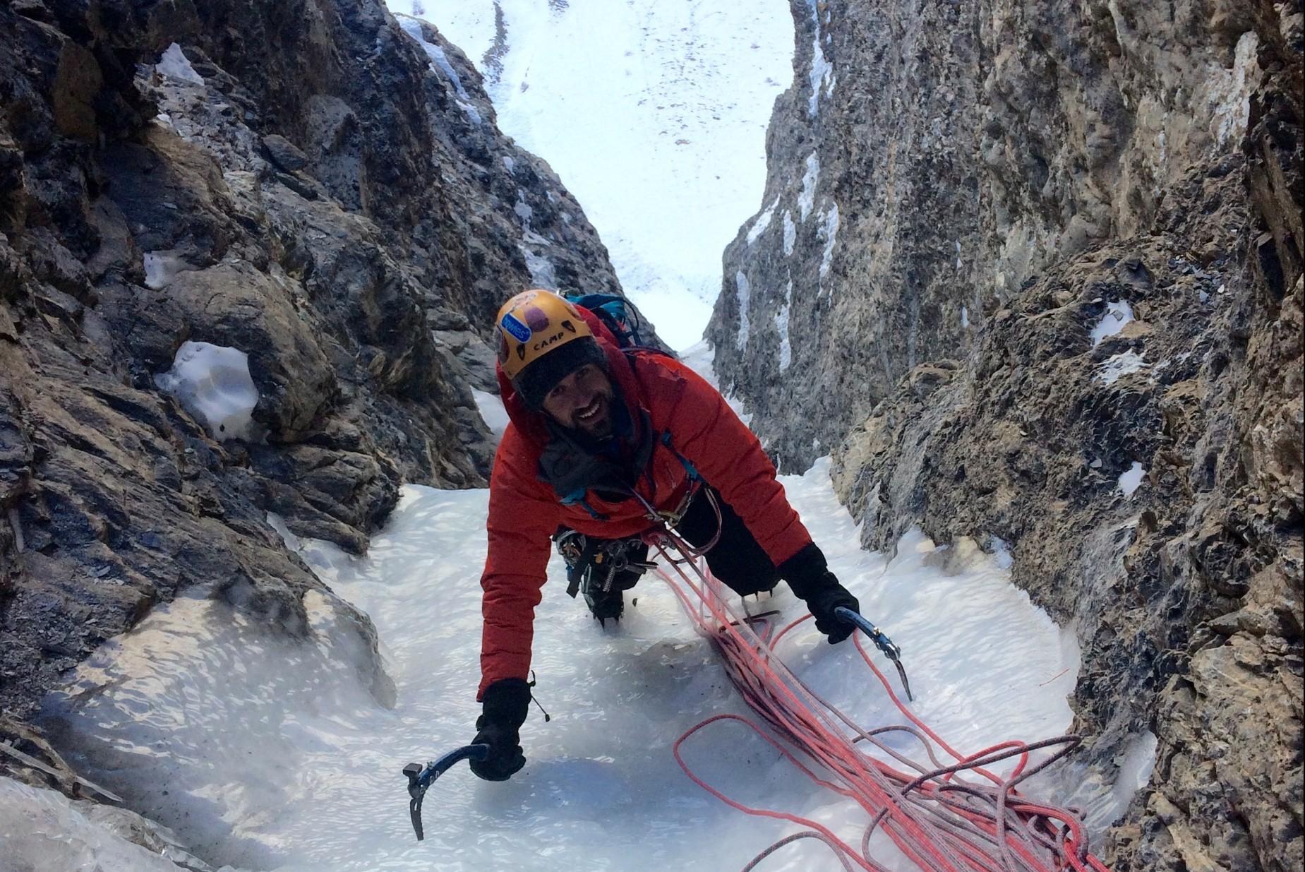 Client content dans la goulotte de sans peur et sans ces pioches encadré par un guide de haute montagne