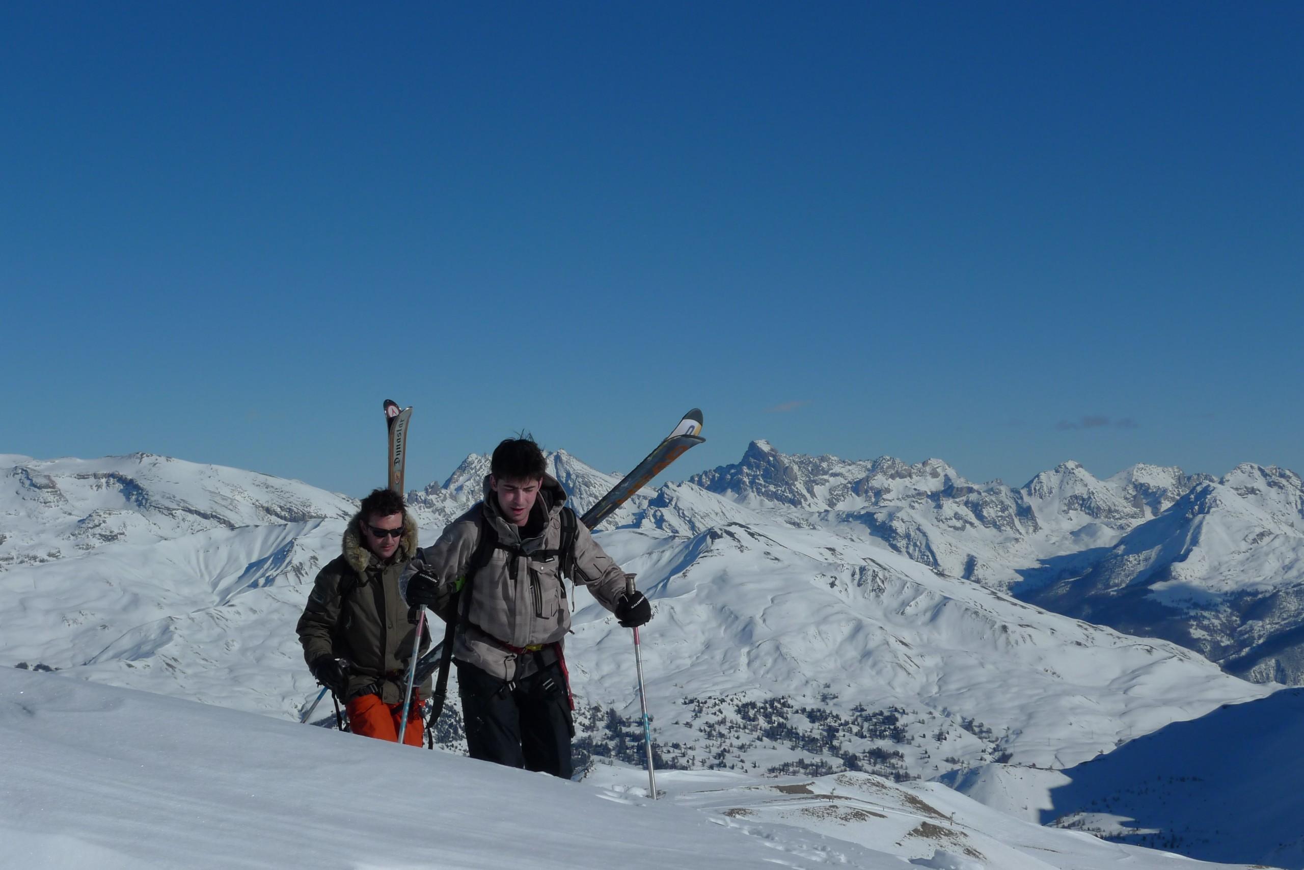 Deux skieurs monte ski sur le dos, avant une descente hors piste sur Vars et Risoul en compagnie de leur guide de montagne.