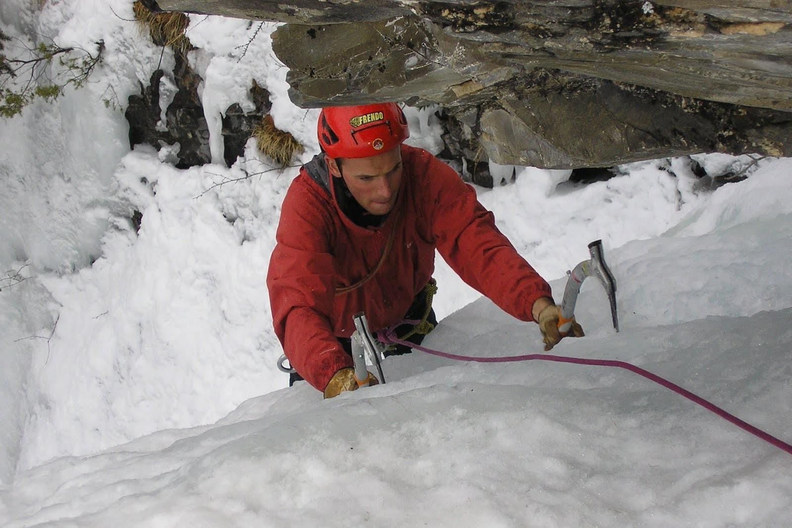 Client qui grimpe un cascade de glace à Ceillac durant une journée cascade de glace Hautes Alpes perfectionneme encadré par un guide de montagne
