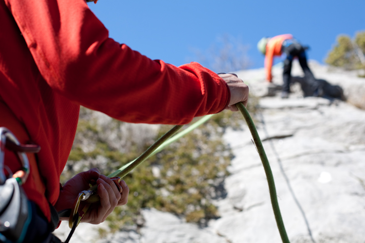 le guide de montagne assure un enfant durant la séance d'initiation escalade. Cette école d'escalade se situe autour de Guillestre.