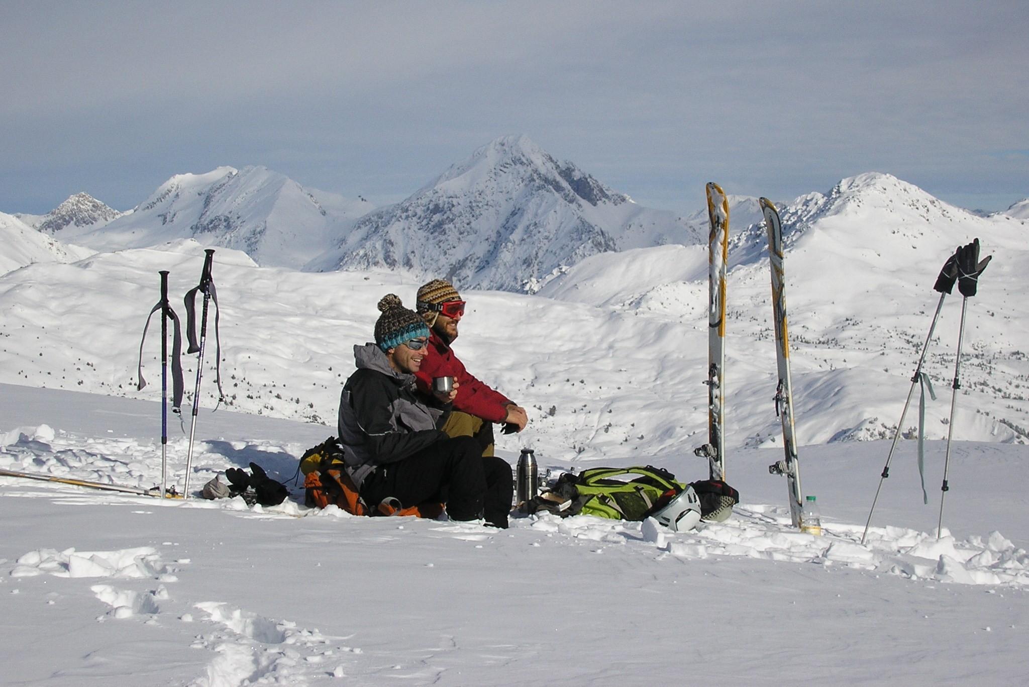 Un guide de montagne et son client contemple la vue durant une journée de ski de randonnée dans le Massif du Queyras dans les Hautes Alpes.