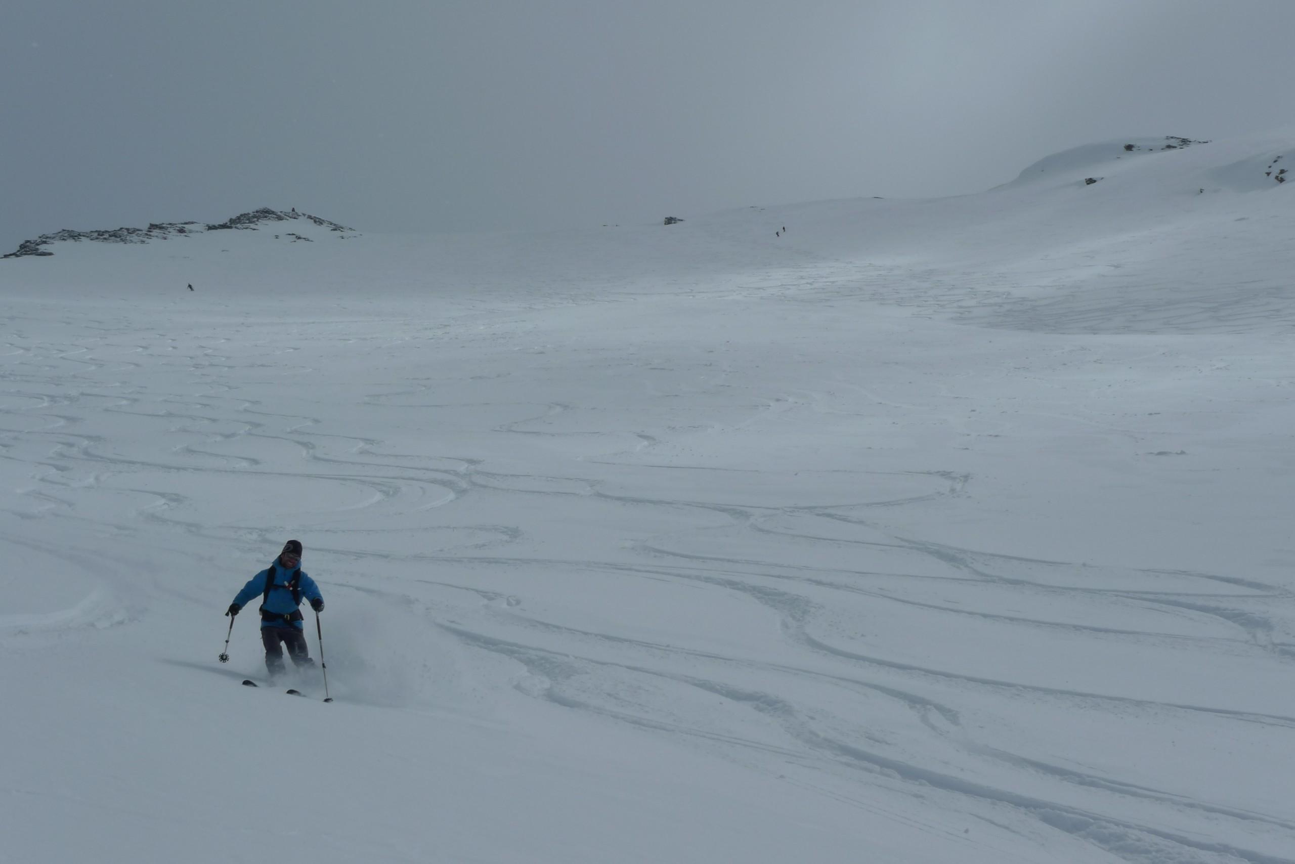 Un skieur hors piste descend un beau vallon plein de neige poudreuse sur Vars et Risoul.