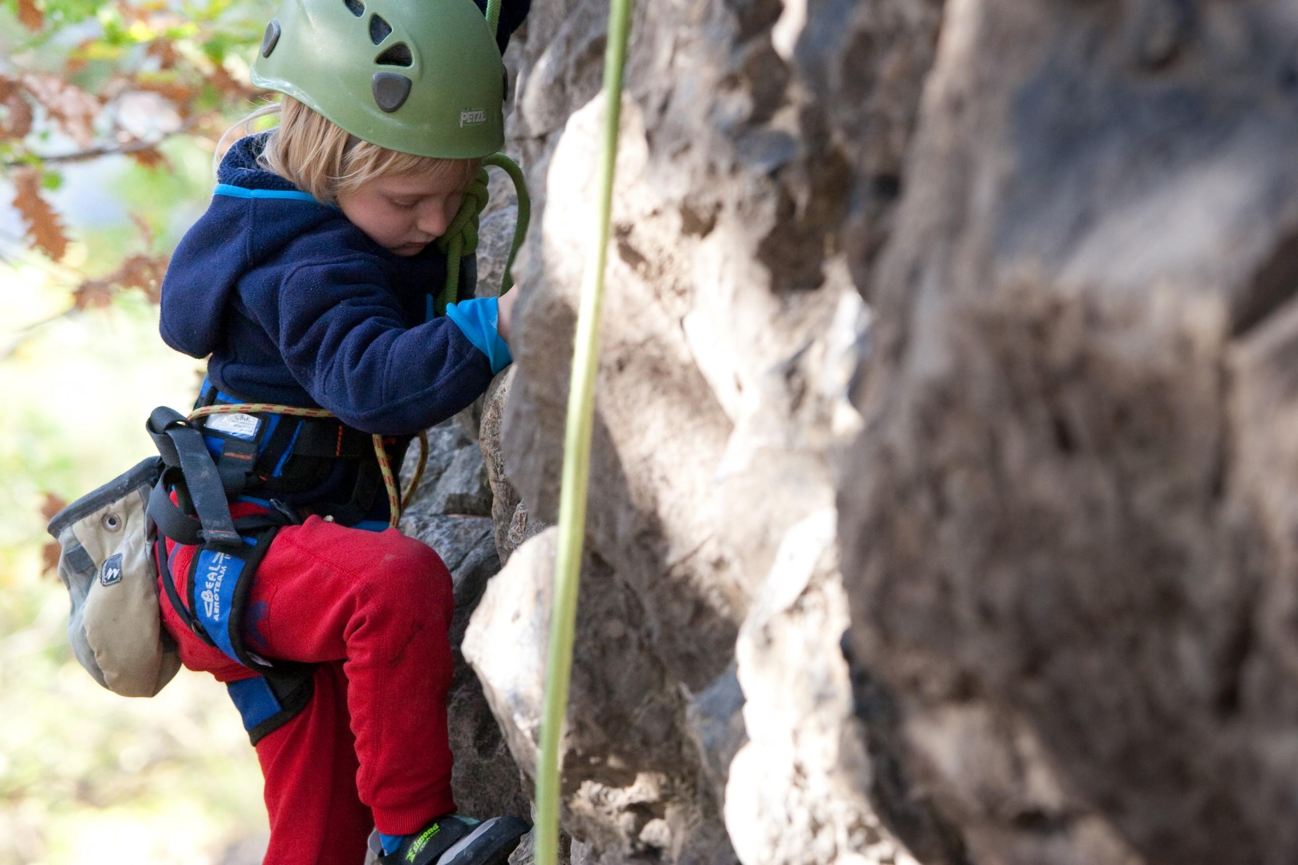 Un enfant grimpe pendant sa première initiation à l'escalade avec un Guide de haute montagne au dessus d'embrun.