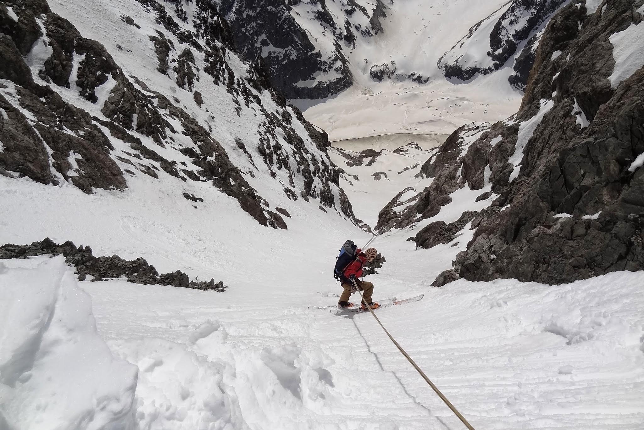 La guide de montagne descend en rappel l'entrée du couloir de la grande sagne lors de la traversée mord sud du col de la grande sagne.