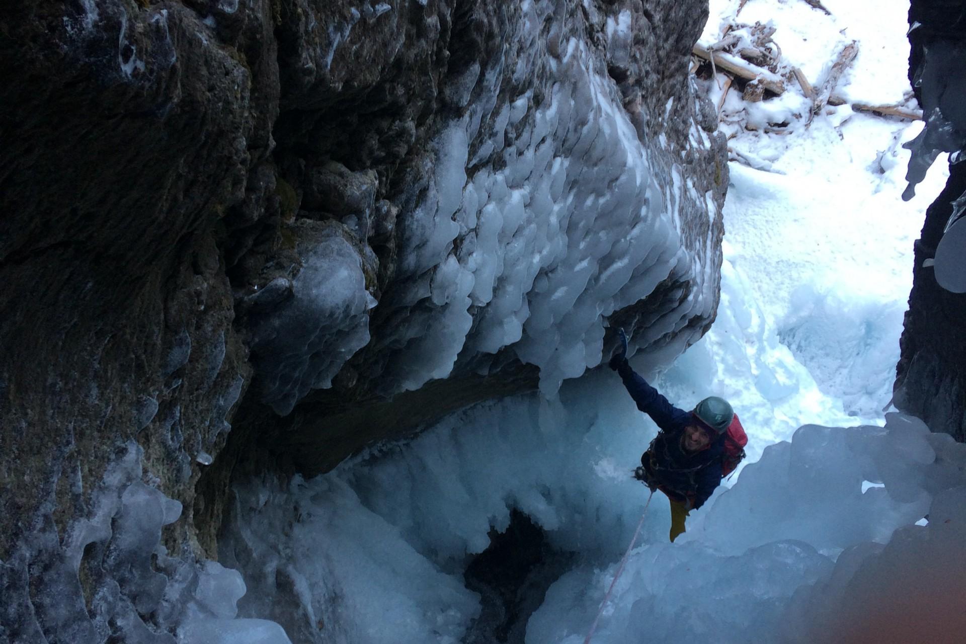 """Avant derrière longueur de la cascade de glace """"Les formes du chaos"""". Le guide assure son client dans une belle étroiture de rocher."""