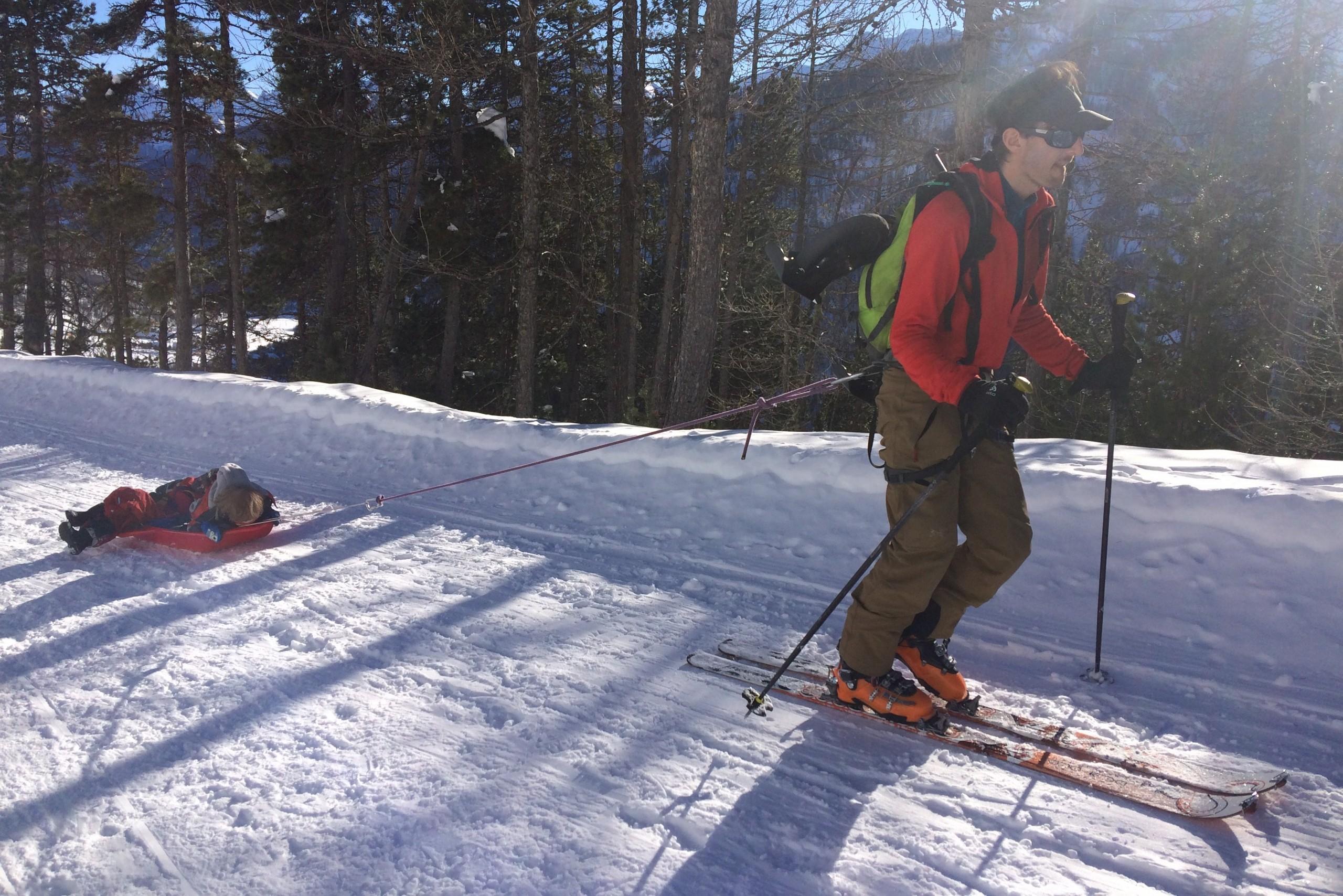 Le guide de haute montagne tracte ses enfants qui joue dans la luge avant une superbe descente