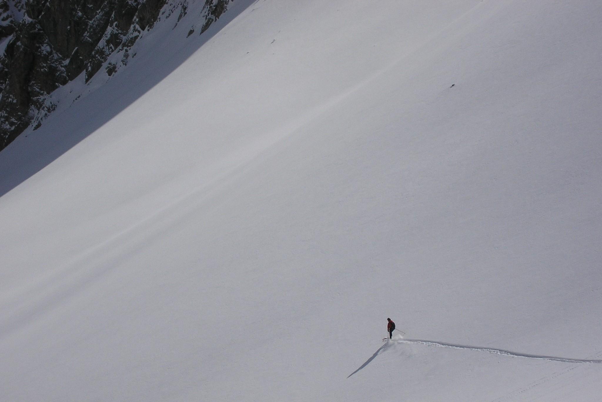 Skieur qui descend une pente vierge durant un raid à ski dans les Hautes-Alpes