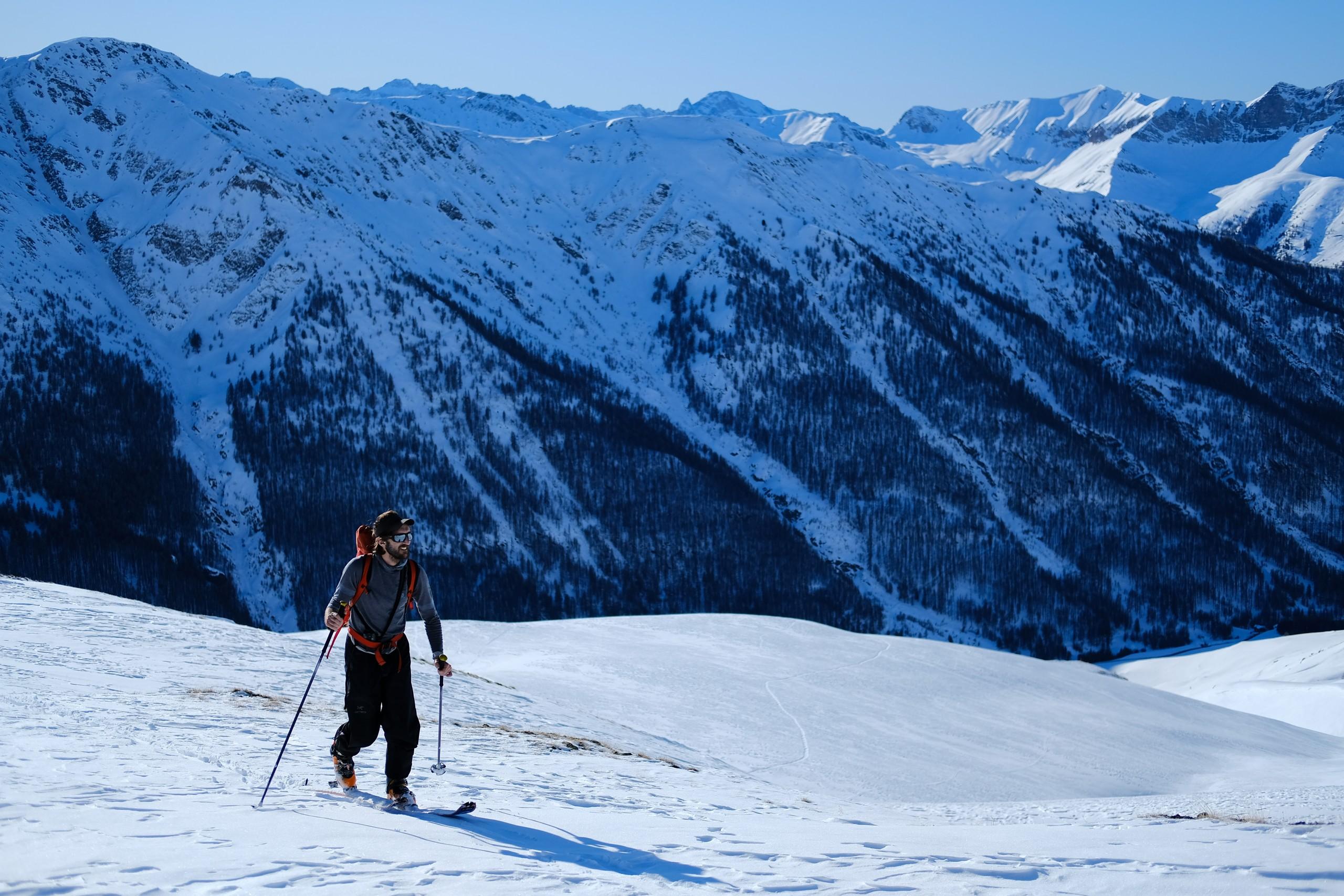 Antonin, guide de montagne remonte en ski de randonnée le pic de fond de peynin avant de basculer sur Aiguilles dans le Queyras